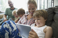 Family relaxing using digital tablet on living room sofa - HEROF05379