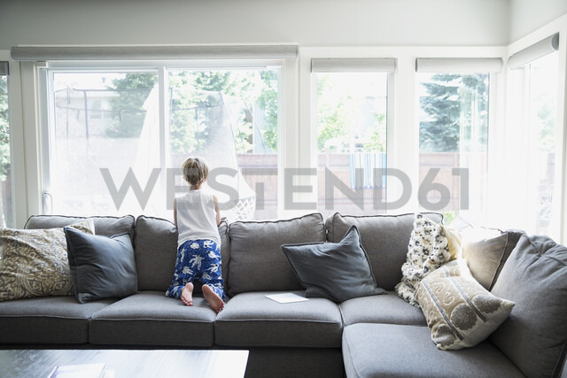 Curious boy in pajamas on sofa looking out living room window - HEROF05382