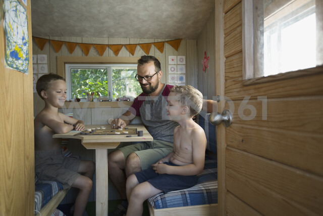 Father and sons playing checkers at table in treehouse - HEROF05388