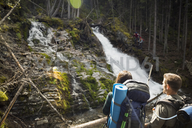 Couple hiking with backpacks enjoying waterfall view in woods - HEROF05391