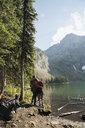 Couple hiking enjoying tranquil, remote mountain lake view - HEROF05394