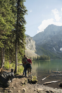 Couple hiking enjoying tranquil, remote mountain lake view - HEROF05394