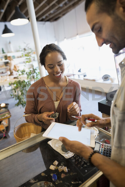 Customer paying shop owner at counter with digital tablet - HEROF05400