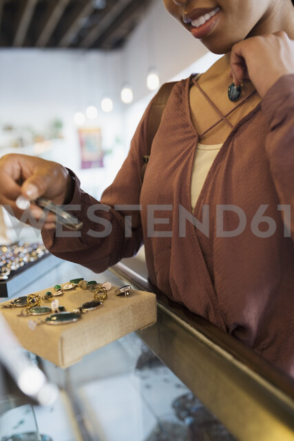 Close up woman browsing jewelry at counter in shop - HEROF05406