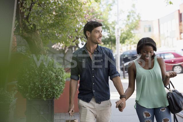 Couple holding hands walking on urban sidewalk - HEROF05409