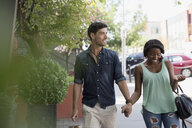 Couple holding hands walking on urban sidewalk - HEROF05409