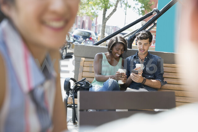 Couple drinking coffee and using cell phone on sunny urban bench - HEROF05412 - Hero Images/Westend61