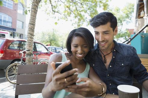 Couple using cell phone at urban sidewalk cafe - HEROF05415