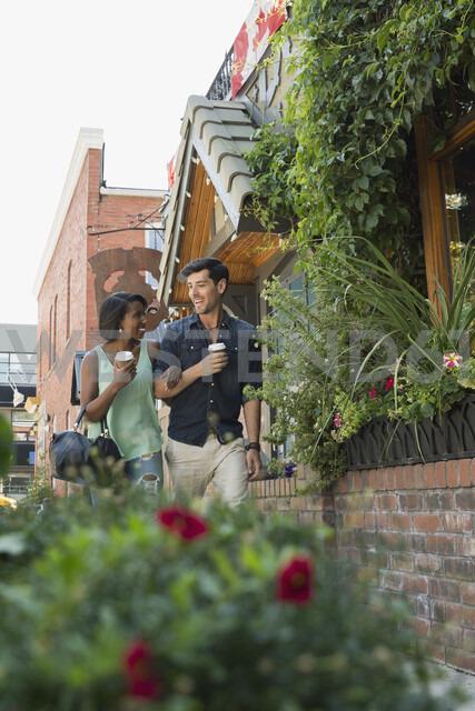Couple walking with coffee on urban sidewalk - HEROF05418 - Hero Images/Westend61