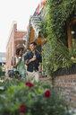 Couple walking with coffee on urban sidewalk - HEROF05418