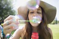 Close up woman in hat blowing bubbles in sunny summer park - HEROF05427