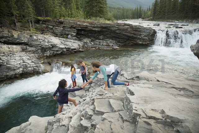 Daughter helping mother climbing rocks near waterfall - HEROF05430 - Hero Images/Westend61