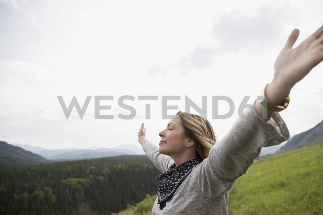 Exuberant woman with eyes closed and arms outstretched in remote rural field - HEROF05436