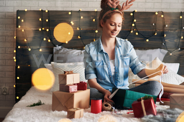 Woman wrapping Christmas presents on bed - CUF48166