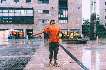 Man welcoming rain in town square, Milan, Italy - CUF48181