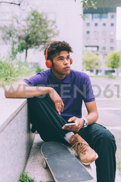 Skateboarder using headphones on concrete bench, Milan, Italy - CUF48193