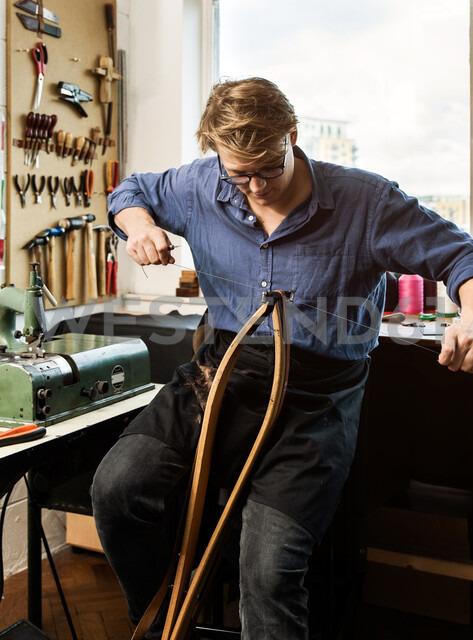 Leatherworker stitching leather handbag straps in workshop - CUF48214