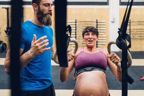 Trainer guiding pregnant woman using exercise equipment in gym - CUF48217