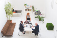 Businessmen and woman using laptops at office meeting, high angle view - CUF48223