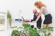 Businesswoman and man looking at laptop on office desk - CUF48226
