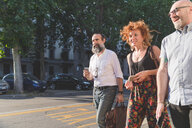 Mid adult woman and male friends chatting while strolling on city sidewalk - CUF48235