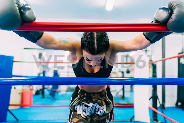 Exhausted female boxer leaning over boxing ring ropes - CUF48241