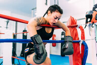 Exhausted female boxer leaning over boxing ring ropes - CUF48244