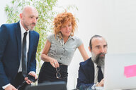 Businesswoman and men looking at laptop on office desk - CUF48259