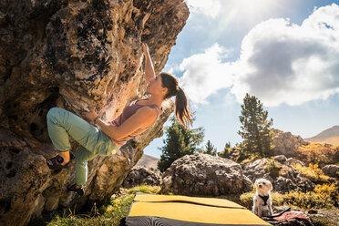 Woman bouldering with her dog watching, Città dei Sassi or Steinerne Stadt, Dolomites - CUF48289