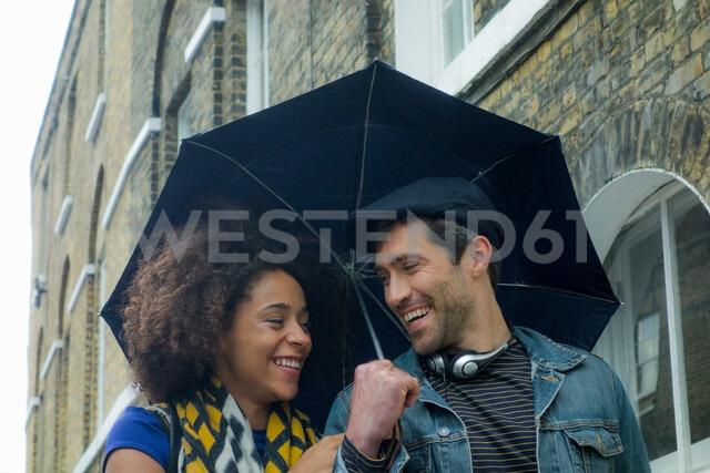 Happy couple under umbrella in street, London, UK - CUF48325