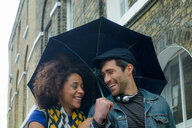 Happy couple under umbrella in street, London, UK - CUF48325