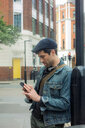 Man texting by lamp post, London, UK - CUF48328