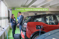 Man and woman charging electric car at charge bay, Manchester, UK - CUF48337