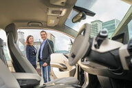 Portrait of man and woman owners of electric car, Manchester, UK - CUF48340