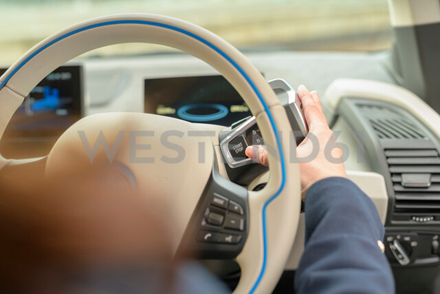 Woman pressing start button on electric car - CUF48343