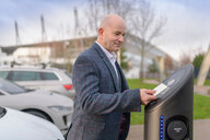 Businessman using access card at electric car charging point, Manchester, UK - CUF48349