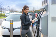 Sportswoman at electric car charging point, Manchester, UK - CUF48352