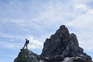 Hiker on peak of rock, Mont Cervin, Matterhorn, Valais, Switzerland - CUF48382