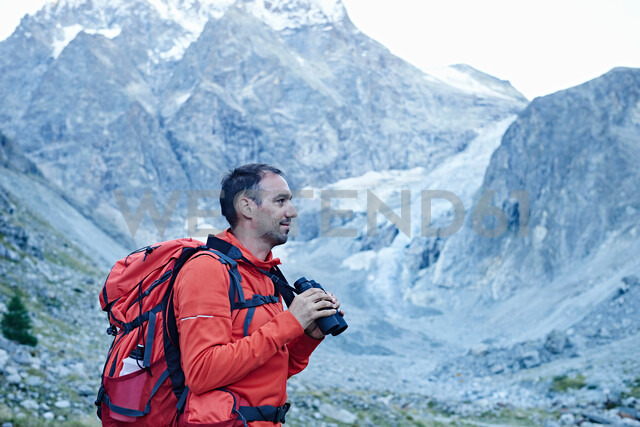 Hiker using binoculars, Mont Cervin, Matterhorn, Valais, Switzerland - CUF48385