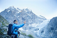 Hiker taking photograph, Mont Cervin, Matterhorn, Valais, Switzerland - CUF48388