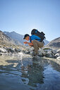 Hiker drinking from pool, Mont Cervin, Matterhorn, Valais, Switzerland - CUF48391