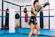 Female boxer practising in boxing ring - CUF48409