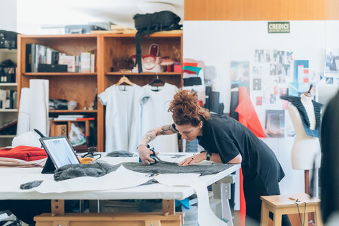 Fashion designer cutting fabric from dressmaker's pattern - CUF48415