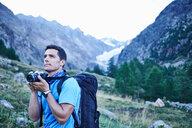 Hiker taking photograph, Mont Cervin, Matterhorn, Valais, Switzerland - CUF48421