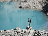 Hiker on rock by edge of lake, Mont Cervin, Matterhorn, Valais, Switzerland - CUF48430