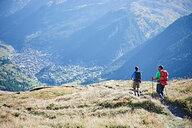Hikers on grassy cliff overlooking valley, Mont Cervin, Matterhorn, Valais, Switzerland - CUF48433
