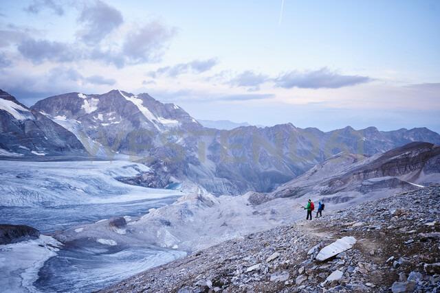 Hiker friends looking at glacier, Mont Cervin, Matterhorn, Valais, Switzerland - CUF48448
