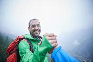 Hikers congratulating themselves, Mont Cervin, Matterhorn, Valais, Switzerland - CUF48454