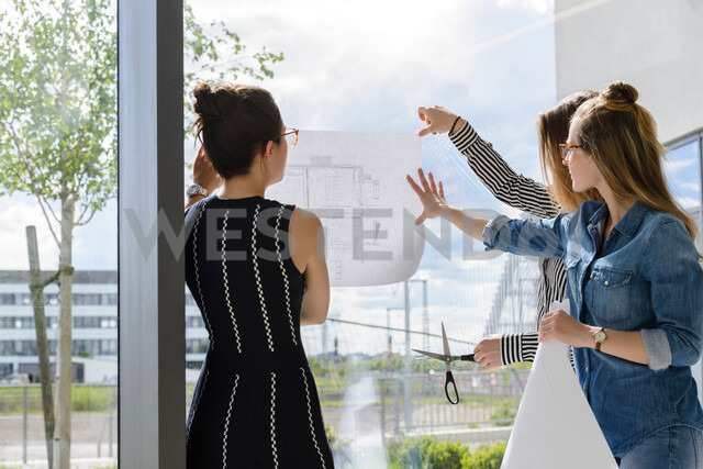 Colleagues discussing plans on glass wall - CUF48472