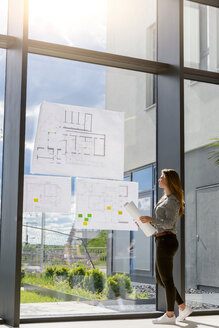 Woman contemplating plans on glass wall - CUF48478